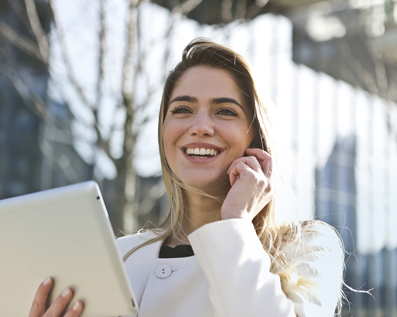 Business woman smiling and talking on the phone while holding a tablet